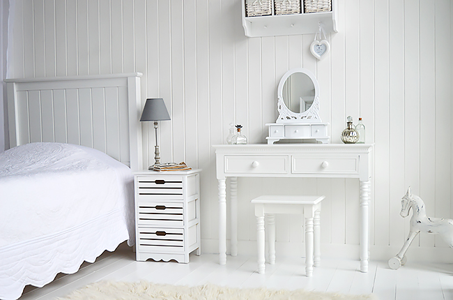 The New England vanity dresser in a pure white bedroom with bedside table, mirror, stool and white accessories