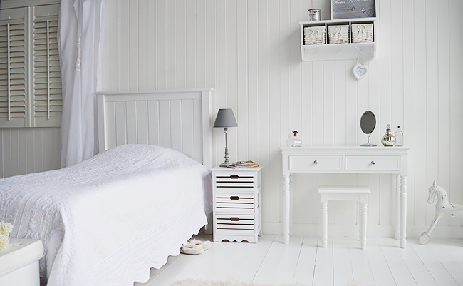 White bedroom with dresser with drawers and bedside with white accessories. Storage bedroom furniture
