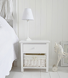 A painted white two drawer storage unit. The bottom drawer is a white lined willow basket, the top drawer has a simple knob pull handle