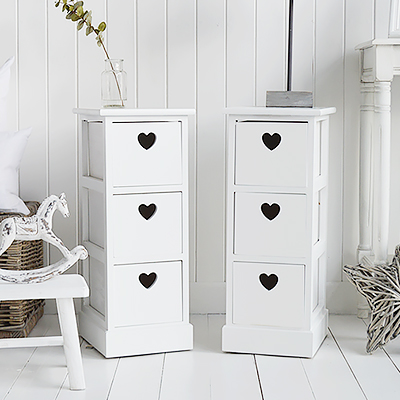 A pair of narrow white bedside tables with three drawers and cut out hearts 25cm wide
