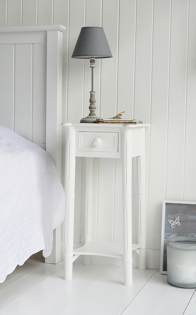 New England bedside table with chunky white handles on the drawers and a shelf