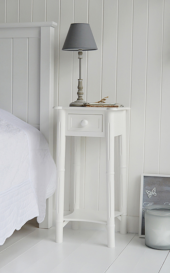 New England white tall bedside table with chunky white handles on the drawers and a shelf