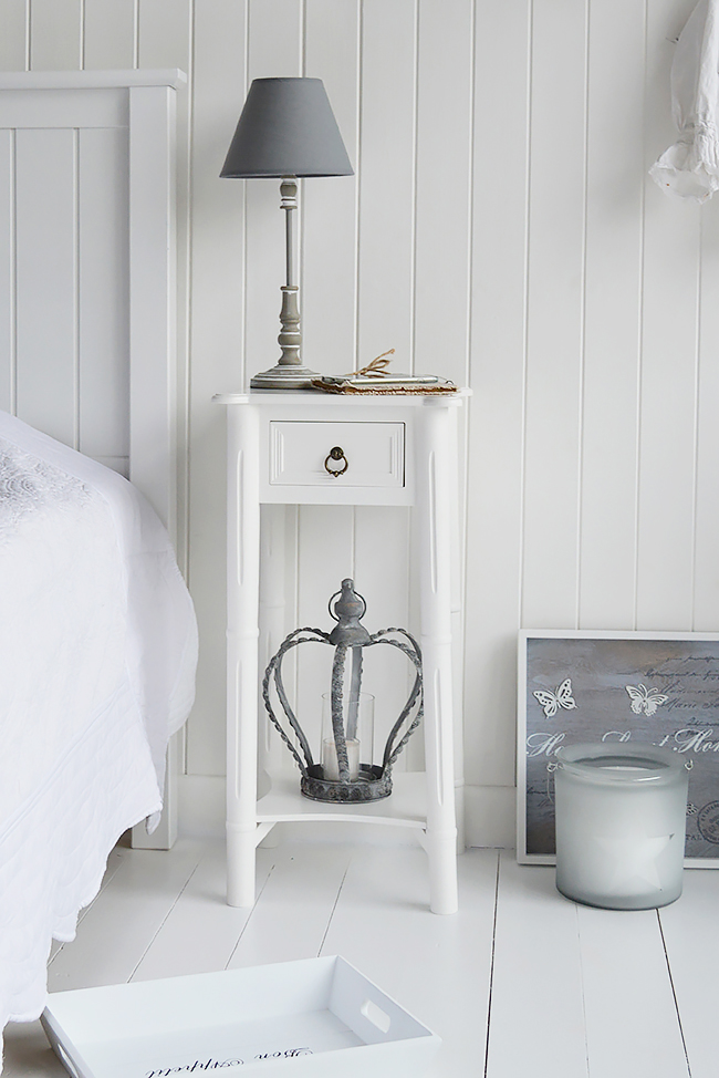A white bedside table with a single drawer with an antique brass drop pull handle and a bottom shelf.
