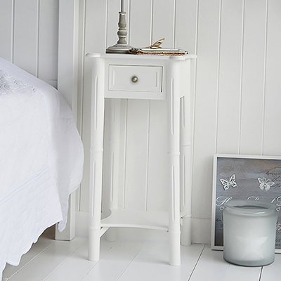 Classic New England white living room furniture. A  tall lamp table with shelf and drawer