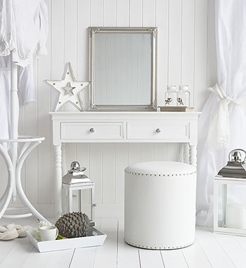 White furniture for a luxury bedroom with dressing table, stool and silver accessories for a boutique hotel interior style.